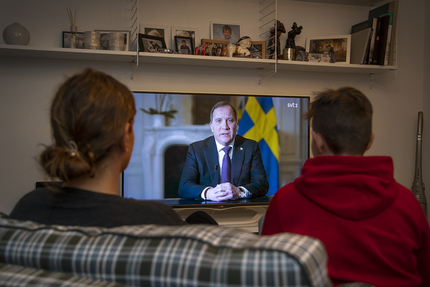 Residents in Stockholm watch Swedish Prime Minister Stefan Lofven address the nation on the COVID-19 pandemic on March 22.