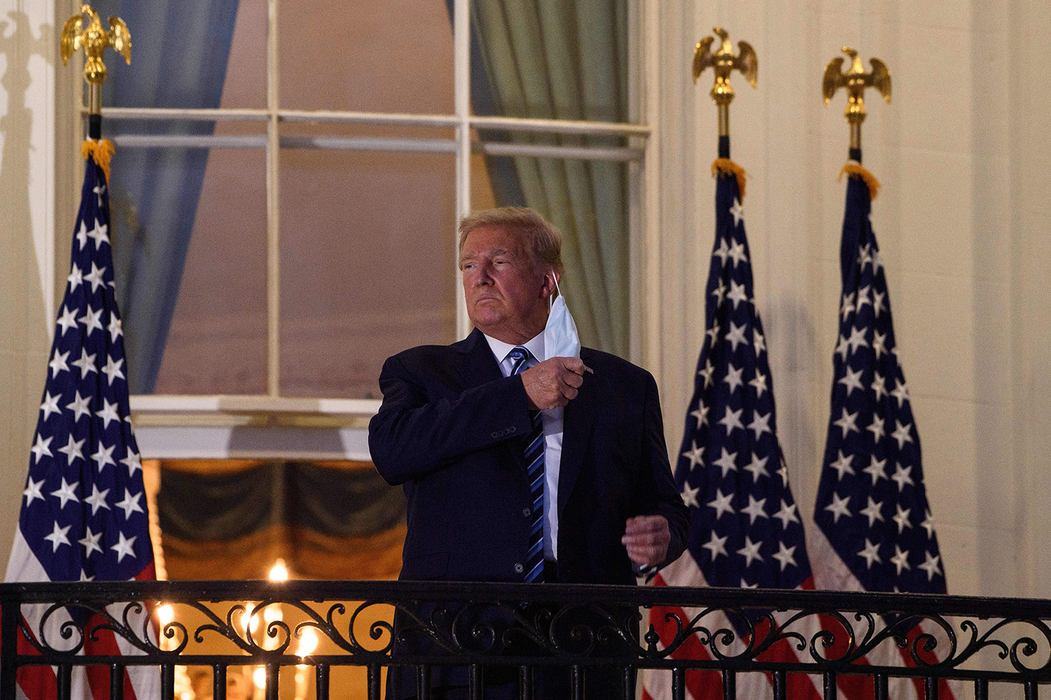 U.S. President Donald Trump takes off his face mask as he arrives at the White House upon his return from Walter Reed Medical Center, where he underwent treatment for COVID-19, in Washington on Oct. 5. NICHOLAS KAMM/AFP via Getty Images