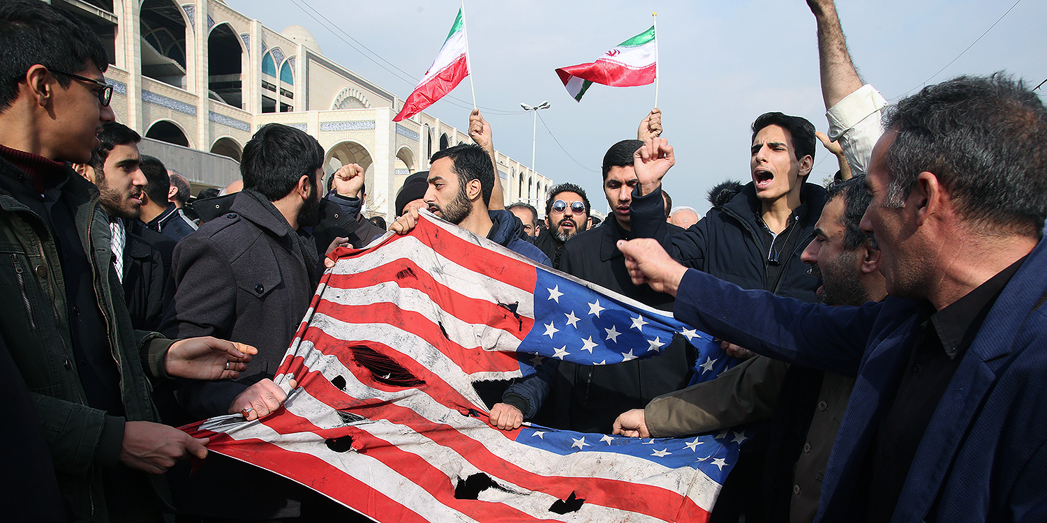 "Iranians tear up a U.S. flag during a demonstration in Tehran on Jan. 3 after Iranian Revolutionary Guard Major General Qasem Soleimani was killed in a U.S. strike on his convoy in Baghdad. Iran warned of ""severe revenge"" and said arch enemy the United States bore responsibility for the consequences after killing one of its top commanders."