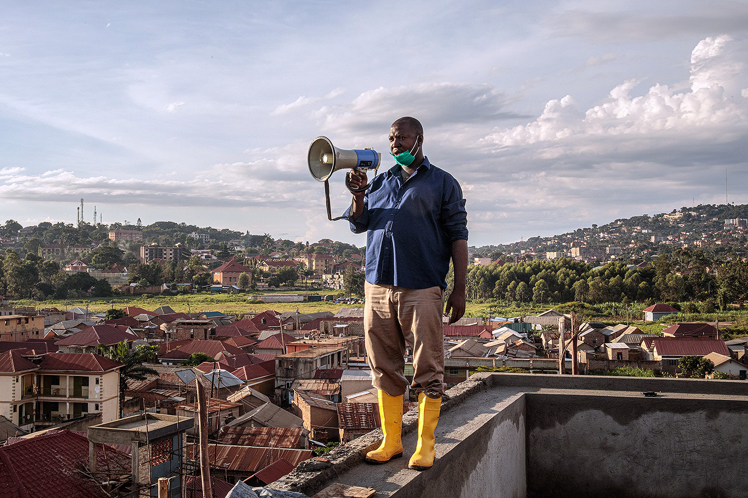 Gonzaga Yiga, a 49-year-old community chairman, makes an appeal to residents through a megaphone from the tallest building in Kampala, Uganda, on March 24. Yiga takes his perch every morning and evening to explain how the coronavirus spreads and how to avoid it. BADRU KATUMBA/AFP via Getty Images
