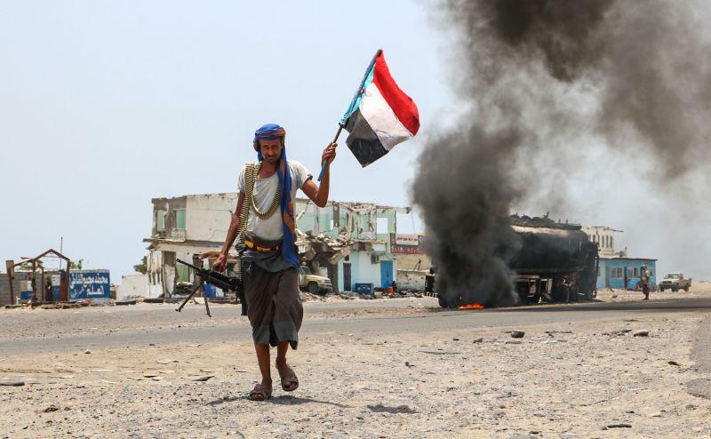 A fighter in Yemen walks past a burning oil tanker.
