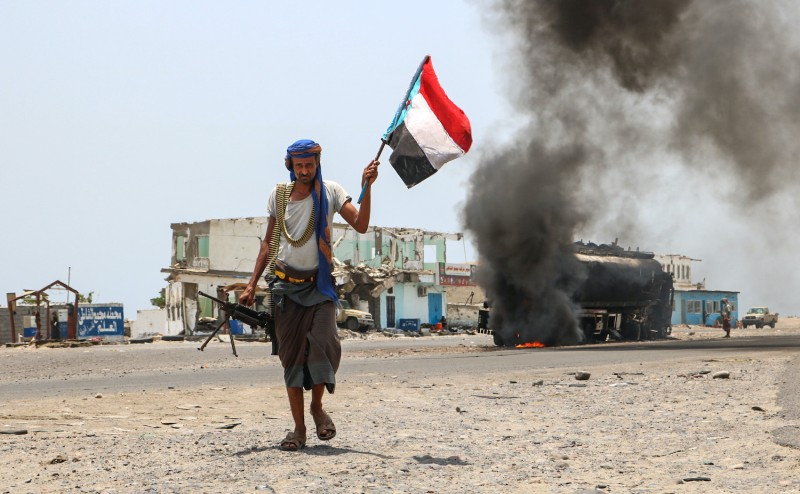 A fighter in Yemen walks past a burning oil tanker.