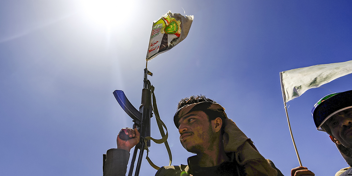 A fighter of the UAE-trained Security Belt Force, dominated by members of the Southern Transitional Council, which seeks independence for south Yemen, walks with a separatist flag past an oil tanker set ablaze during clashes between the separatists and the Saudi-backed government forces in southern Yemen on Aug. 30, 2019.