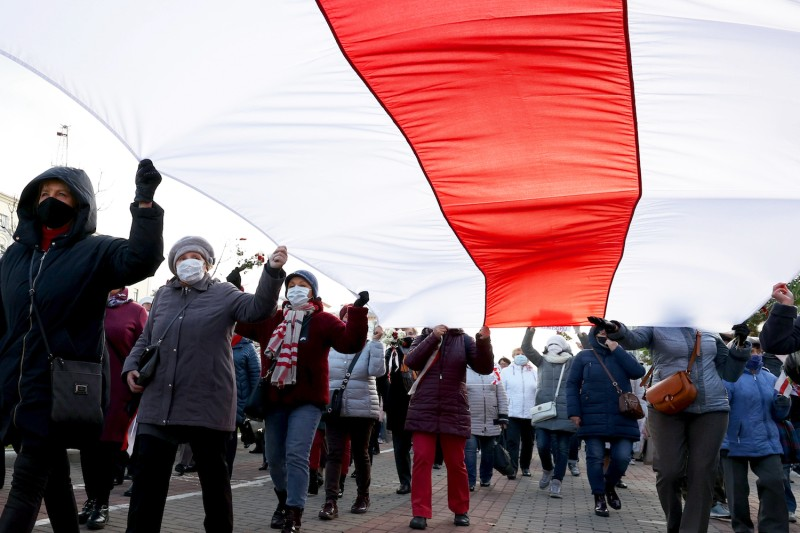 Protesters carry a huge former flag of Belarus during a rally to demand the resignation of President Aleksandr Lukashenko and a new election in Minsk, Belarus, on Oct. 19.