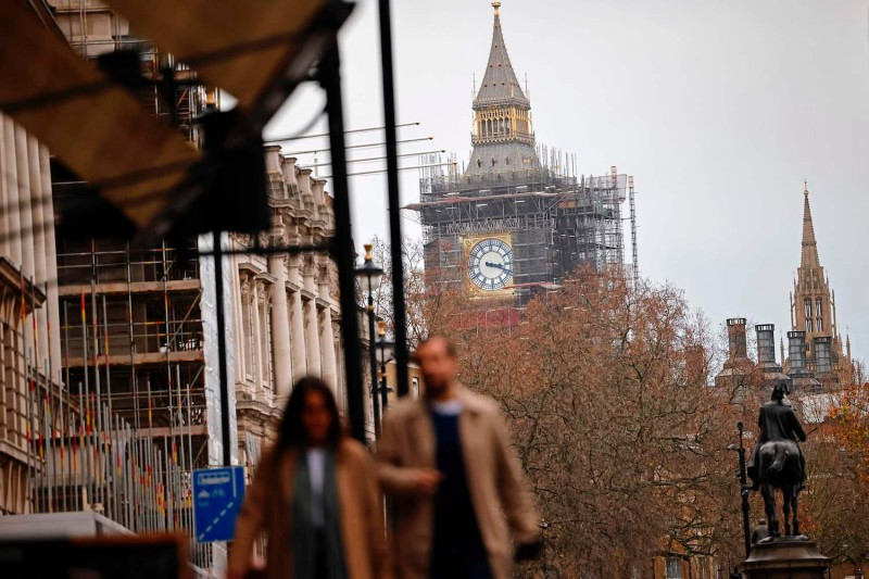 Pedestrians walk away from the Palace of Westminster in central London on December 13, 2020.