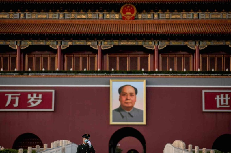 A paramilitary police officer talks on his radio transmitter as he stands in front of the portrait of late communist leader Mao Zedong at Tiananmen Gate in Beijing on Oct. 13.