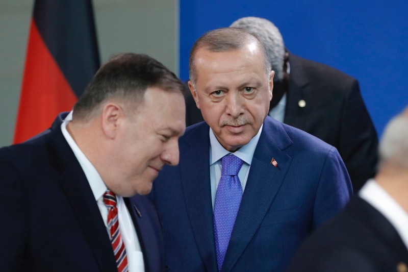 Turkish President Recep Tayyip Erdogan looks on as U.S. Secretary of State Mike Pompeo walks past  during a Peace summit on Libya at the Chancellery in Berlin, on January 19, 2020.