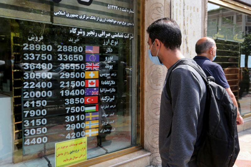An Iranian man checks a display board at a currency exchange shop in Tehran, on Sept. 29.