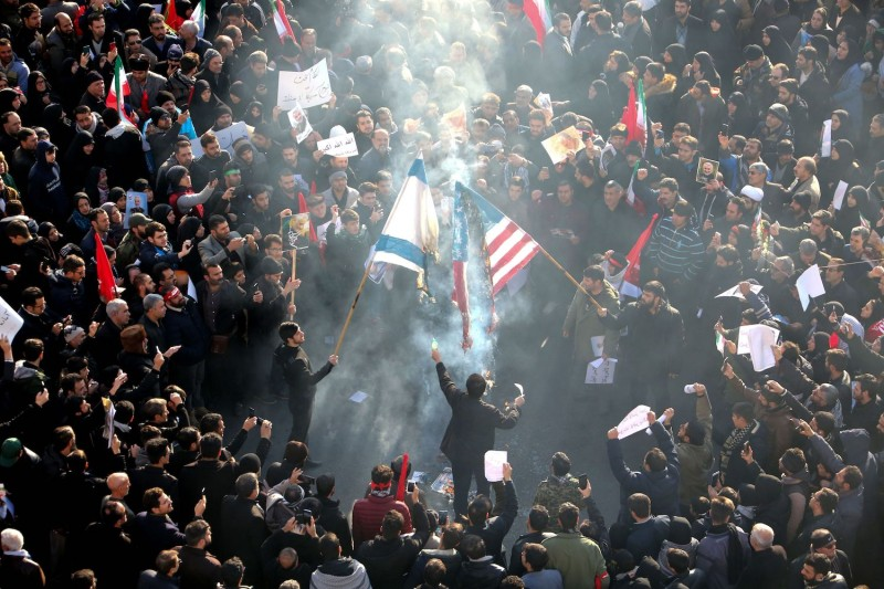 Iranians set a US and an Israeli flag on fire during a funeral procession in Tehran on Jan. 6 for military commander Qassem Suleimani, Iraqi paramilitary chief Abu Mahdi al-Muhandis and others killed by a U.S. attack.
