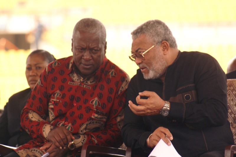 Ghana's then-President John Dramani Mahama (L) talks with former President of Ghana Jerry Rawlings (R) at the Baba Yara stadium in Kumasi on Aug. 30, 2012.