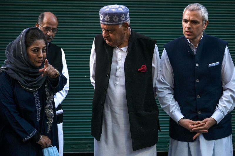 Former Jammu and Kashmir chief minister Mehbooba Mufti (L) gestures while talking with Jammu and Kashmir National Conference President Farooq Abdullah (C) along with his son and former Jammu and Kashmir chief minister Omar Abdullah (R) after a meeting in Srinagar on Oct. 15.