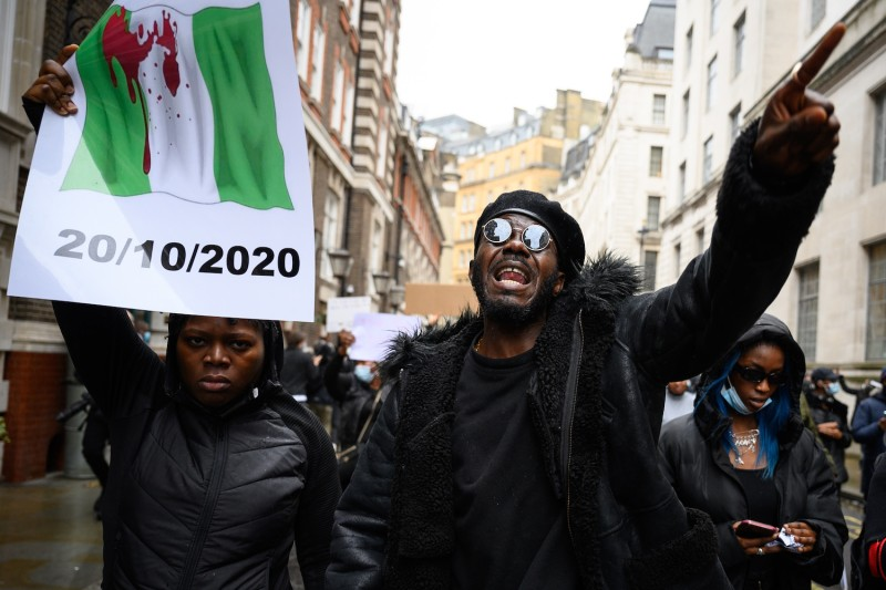 A protester gestures toward the media as he marches with a demonstration calling for the end of police violence in Nigeria, on Oct. 21, 2020 in London, England.