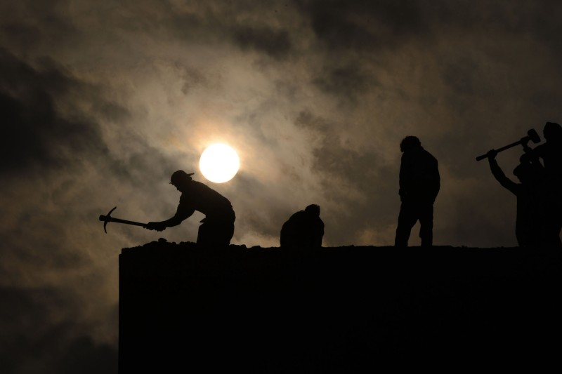Pakistani laborers work on a building in Lahore on Jan. 21, 2014.