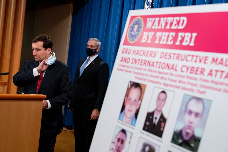 A poster showing six wanted Russian military intelligence officers is displayed as John Demers, aAssistant attorney general for the National Security Division, takes the podium to speak at a news conference at the Department of Justice in Washington on Oct. 19.