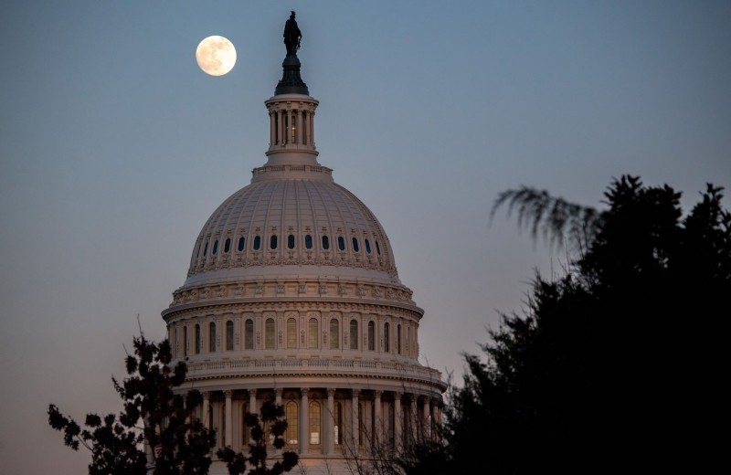 The moon rises over the US Capitol Dome at sunset in Washington, DC, December 28, 2020.