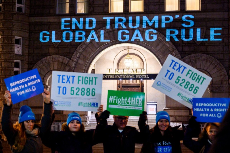 Activists from the Population Connection Action Fund hold signs as they project a message onto the Trump International Hotel to protest the Global Gag Rule in Washington on Jan. 23, 2019.