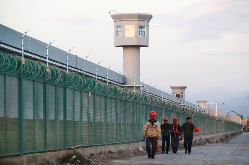 Workers walk by the perimeter fence of what is officially known as a vocational skills education center in Dabancheng in Xinjiang, China, on Sept. 4, 2018.