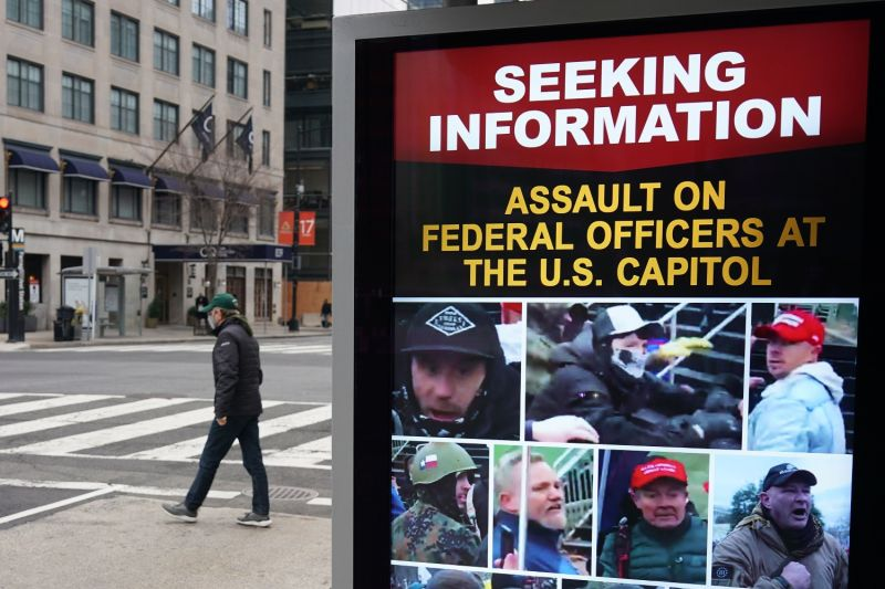 A sign showing images of people wanted in connection with the insurrection at the U.S. Capitol