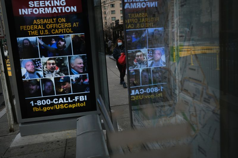 A bus stop advertises faces of people wanted for questioning over violent storming of the U.S. Capitol