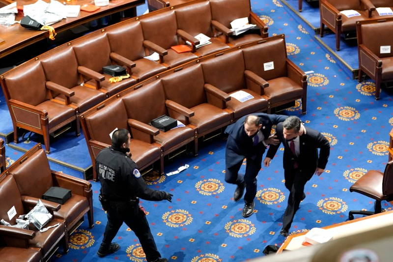 Members of the U.S. Congress run for cover as protesters try to enter the House Chamber during a joint session of Congress in Washington on Jan. 6.