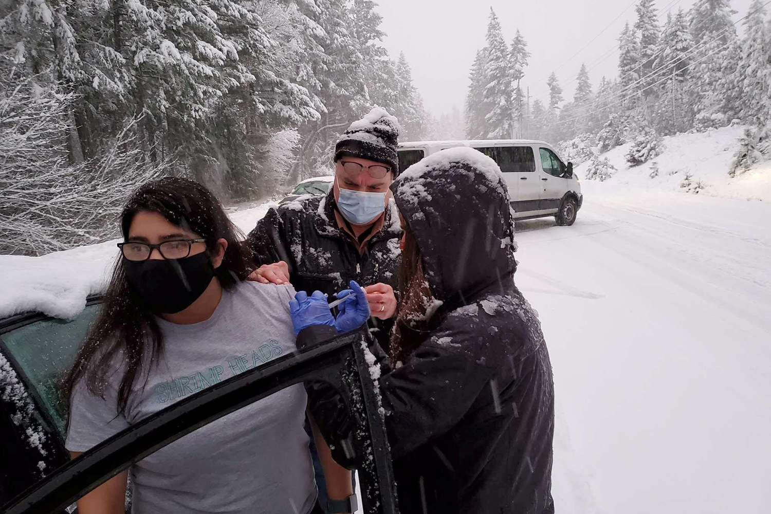 While being stuck in traffic during a snowstorm, Josephine County Public Health staff and volunteers administer COVID-19 vaccinations along Highway 199 in Hayes Hill, Oregon, on Jan. 26. Josephine County Public Health/via REUTERS