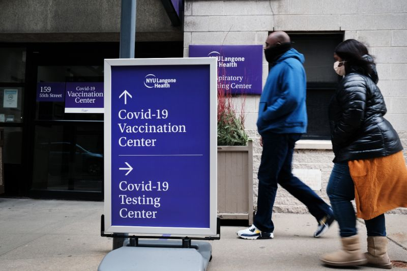 People walk by a sign for both a coronavirus testing clinic and a COVID-19 vaccination location