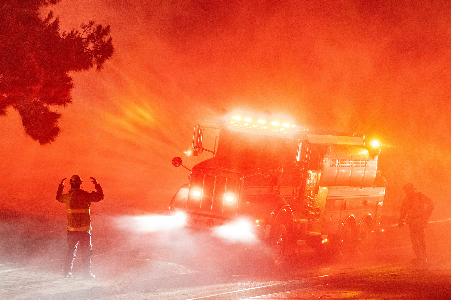 Firefighters fight flames on the side of Interstate 210 in Sylmar, California, on Jan. 19. JOSH EDELSON/AFP via Getty Images