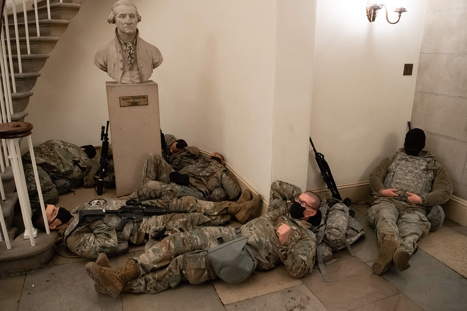 Members of the National Guard rest in the Rotunda of the U.S. Capitol in Washington on Jan. 13, ahead of an expected House vote impeaching President Donald Trump. SAUL LOEB/AFP via Getty Images
