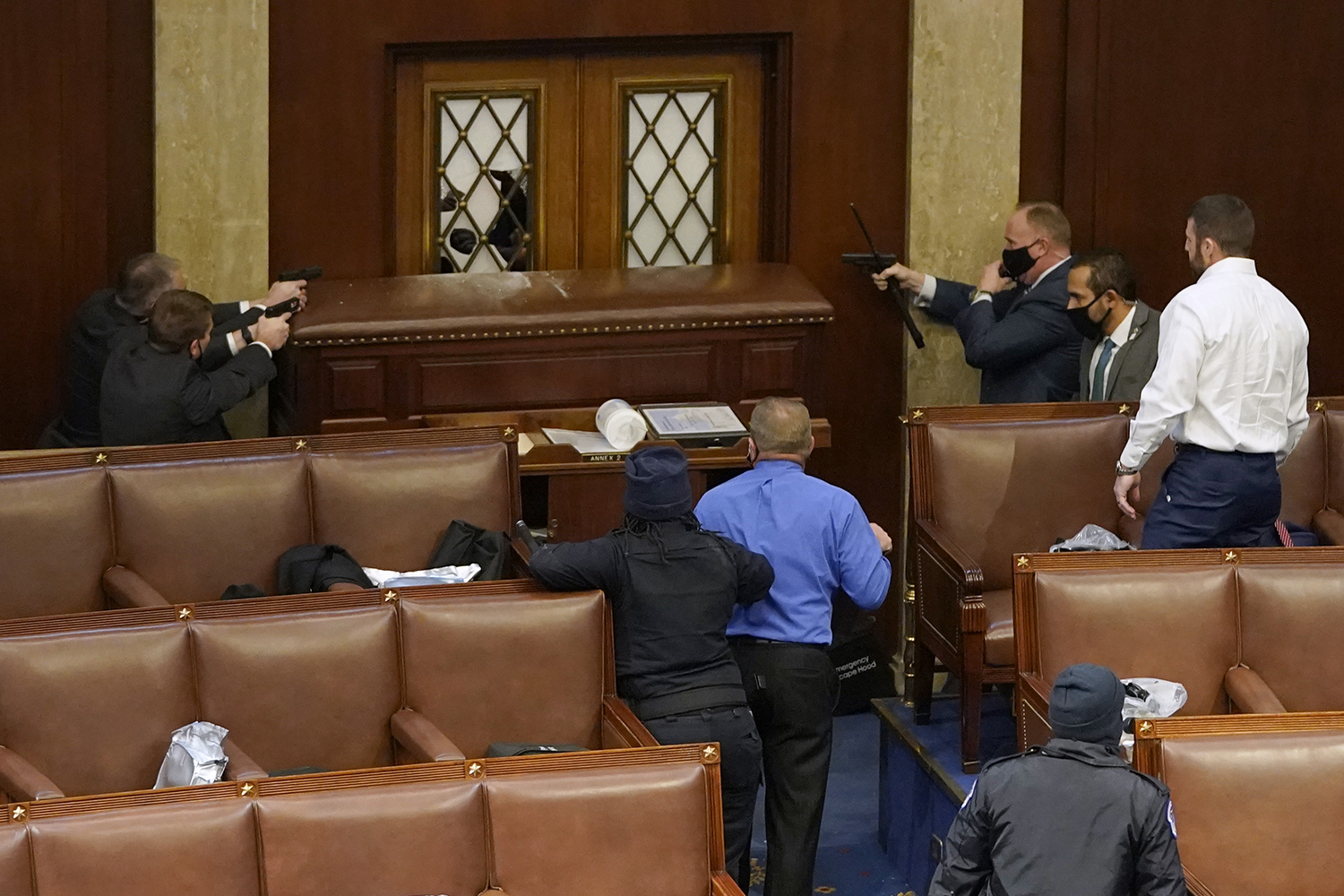 U.S. Capitol police officers point their guns at a door as insurrectionists attempt to get inside the Capitol's House chamber during a joint session of Congress in Washington on Jan. 6. Drew Angerer/Getty Images