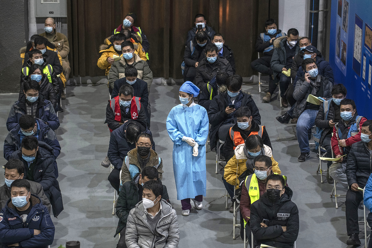 Chinese workers, including security guards, wait to receive a COVID-19 vaccine at a mass vaccination center in Beijing on Jan. 15. Kevin Frayer/Getty Images