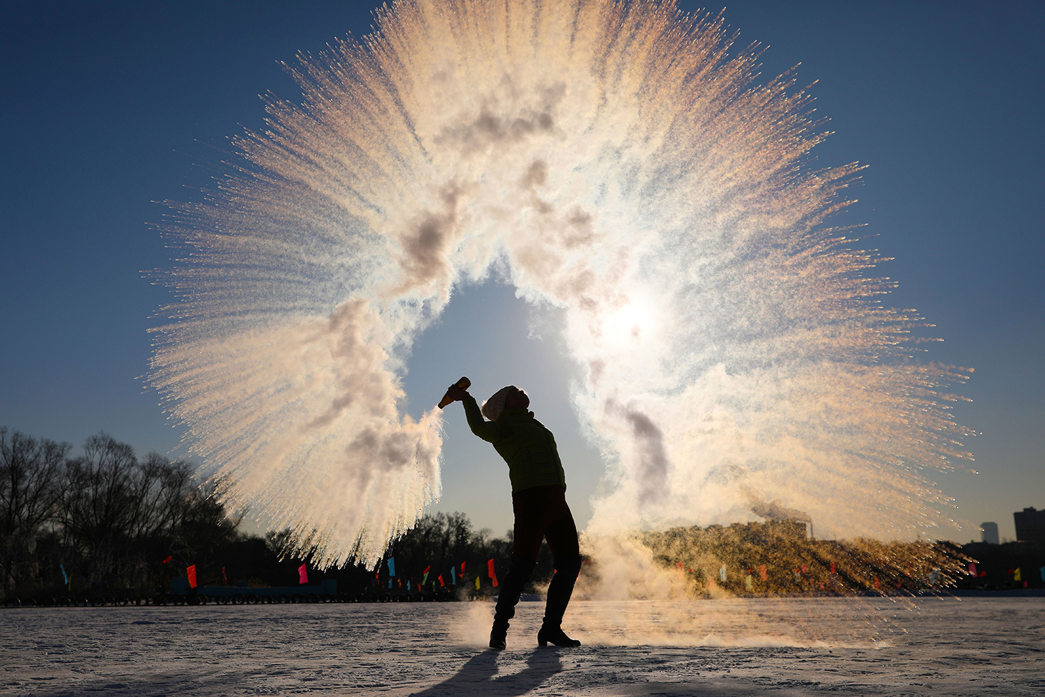 A woman throws hot water into the air and watches as it instantly condenses into ice crystals amid temperatures of minus 17 degrees Fahrenheit in Shenyang, China, on Jan. 8. STR/AFP via Getty Images