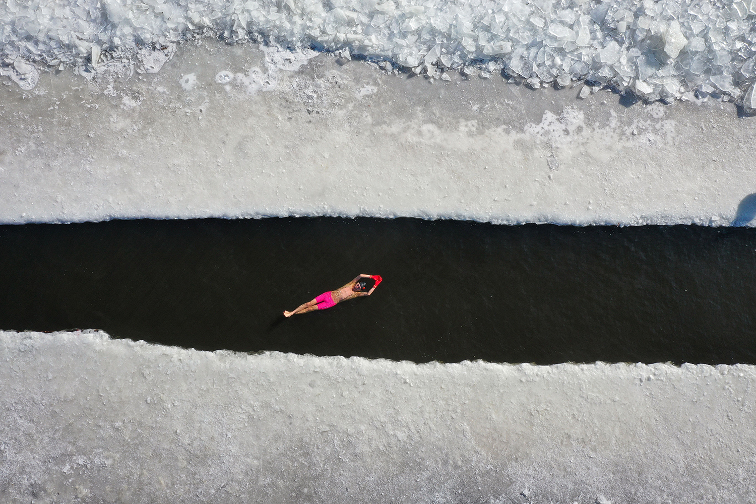 A man swims in a pool that was cut into a frozen lake in Shenyang, China, on Jan. 7. STR/AFP via Getty Images
