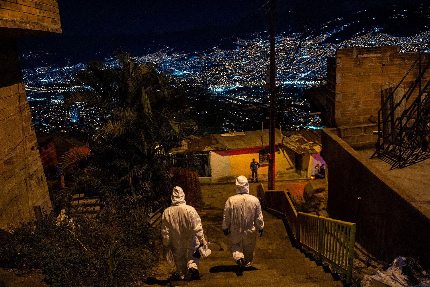 Paramedics leave a home after assisting a patient with symptoms of COVID-19 in Medellin, Colombia, on Jan. 12.  JOAQUIN SARMIENTO/AFP via Getty Images