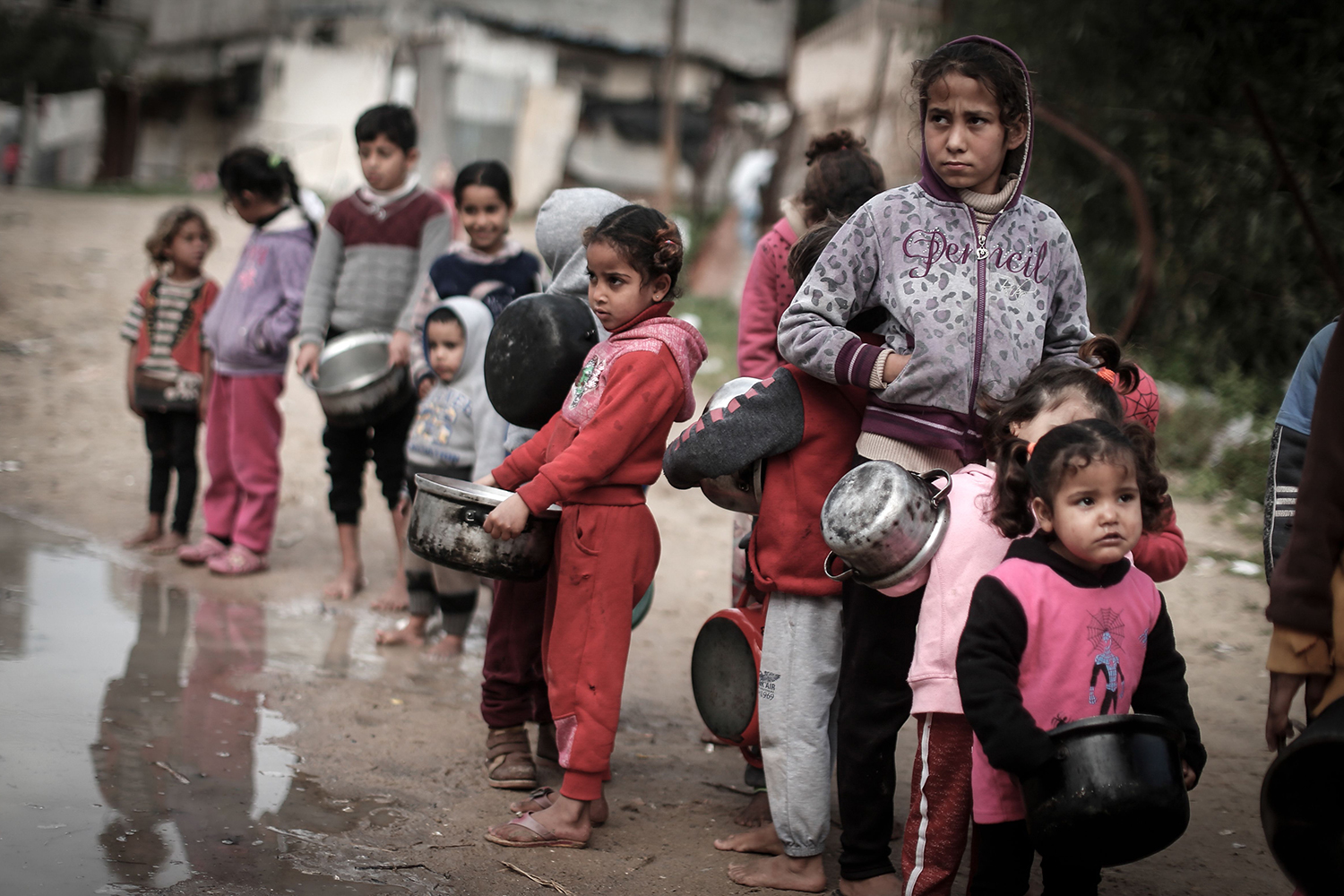 Palestinian children carry pots as they wait to receive a meal in Gaza City on Jan. 28. MAHMUD HAMS/AFP via Getty Images