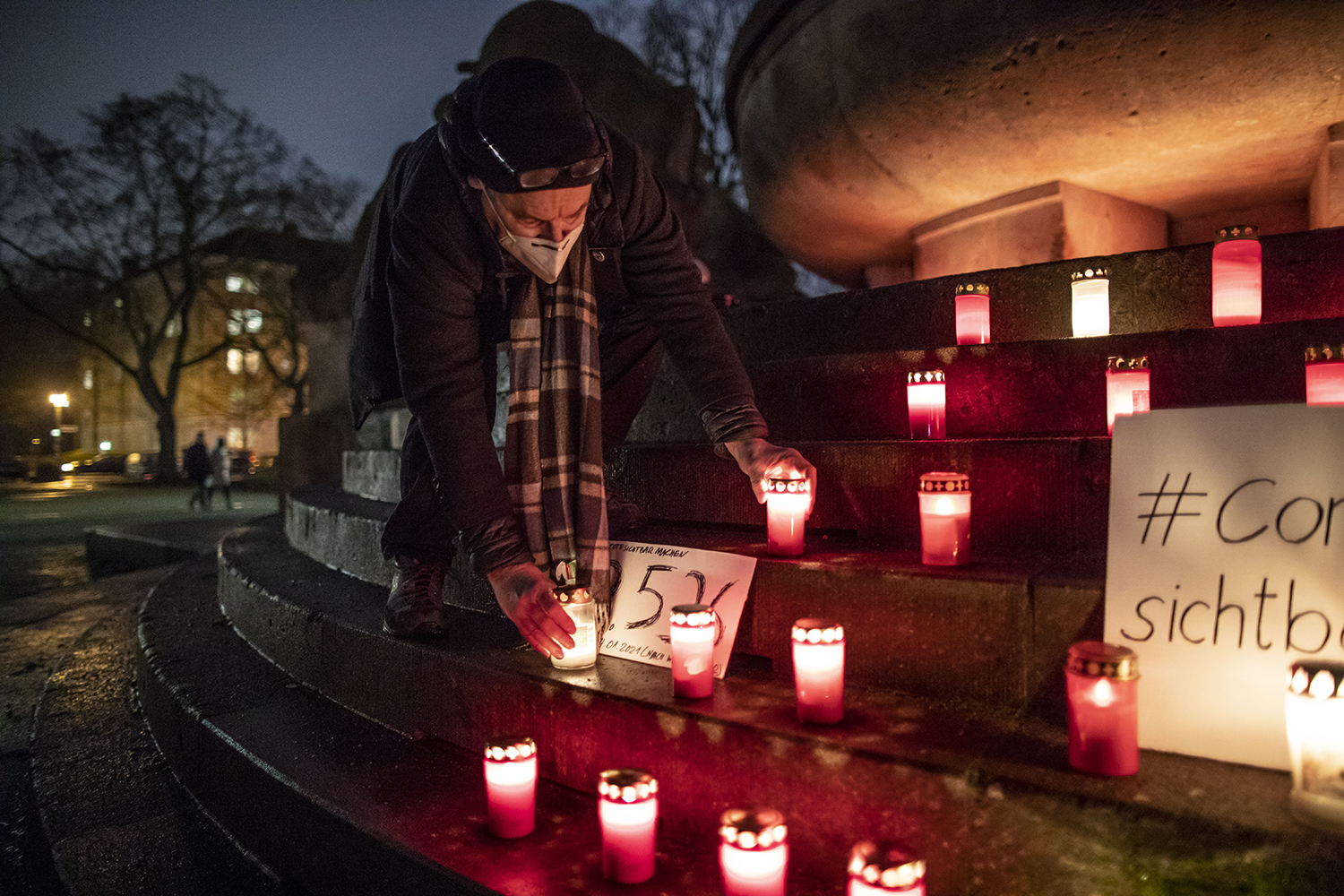 Christian Y. Schmidt arranges candles at a makeshift memorial for COVID-19 victims at Arnswalder Platz in Berlin on Jan. 24. The death toll in Germany has surpassed 55,000. Omer Messinger/Getty Images