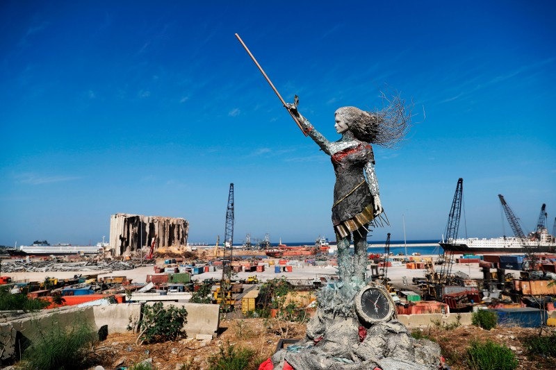 A statue of a woman by Lebanese artist Hayat Nazer, made out of leftover glass, rubble, and a broken clock marking the time (6:08 PM) of the mega explosion at the port of Beirut is placed opposite to the site of the blast in the Lebanese capital's harbour, to mark the one year anniversary of the beginning of the anti-government protest movement across the country, on October 20, 2020.