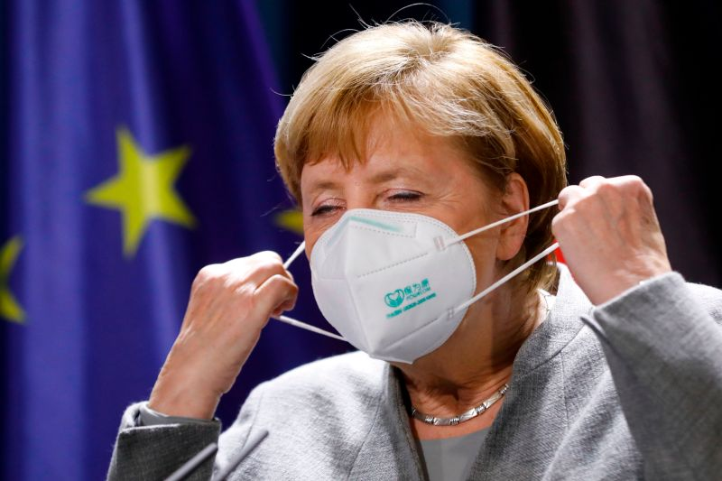 German Chancellor Angela Merkel takes off her face mask as she arrives for a a virtual news conference on security issues with French President Emmanuel Macron, Austrian Chancellor Sebastian Kurz, Netherlands Prime Minister Mark Rutte, European Commission President Ursula von der Leyen and European Council President Charles Michel, at the Chancellery in Berlin on Nov. 10, 2020.