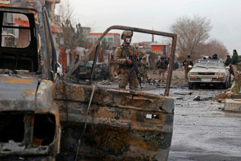 A member of Afghan security force stands guard at the site of an attack in Kabul on Dec. 20, when a car bomb targeting an Afghan lawmaker killed nine people and wounded more than a dozen others.