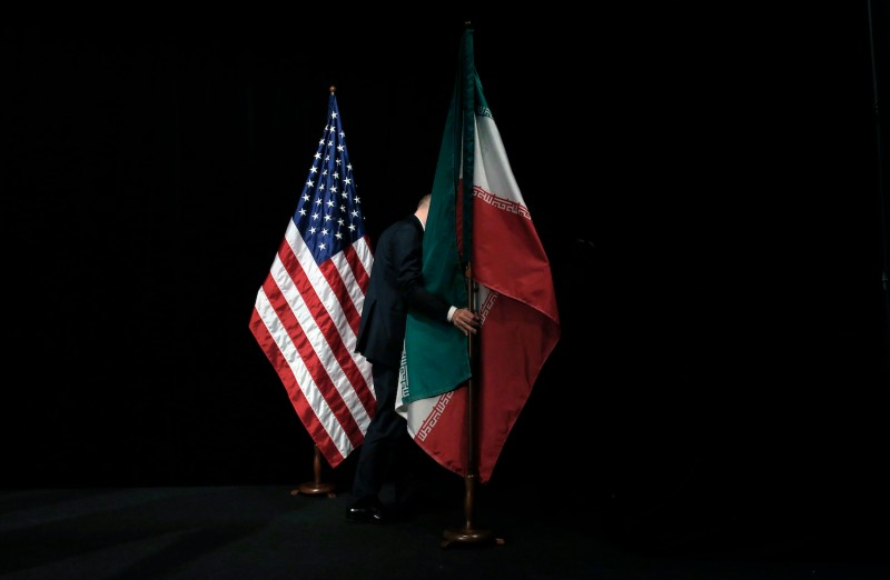 A staff removes the Iranian flag from the stage after a group picture with foreign ministers and representatives of Unites States, Iran, China, Russia, Britain, Germany, France and the European Union during the Iran nuclear talks at Austria International Centre in Vienna, Austria on July 14, 2015.