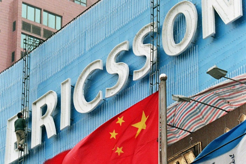 Workers raise a giant Ericsson signboard on top of a building in Beijing on Nov. 25, 1997.