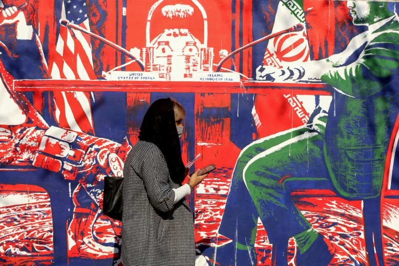 An Iranian woman wearing a protective mask walks past a mural painted on the outer walls of the former U.S. embassy in Tehran, on Dec. 30, 2020.
