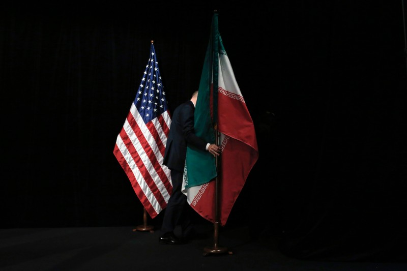 A staff member positions an Iranian flag on a stage after a group picture during the Iran nuclear talks at Vienna International Centre in Austria on July 14, 2015.