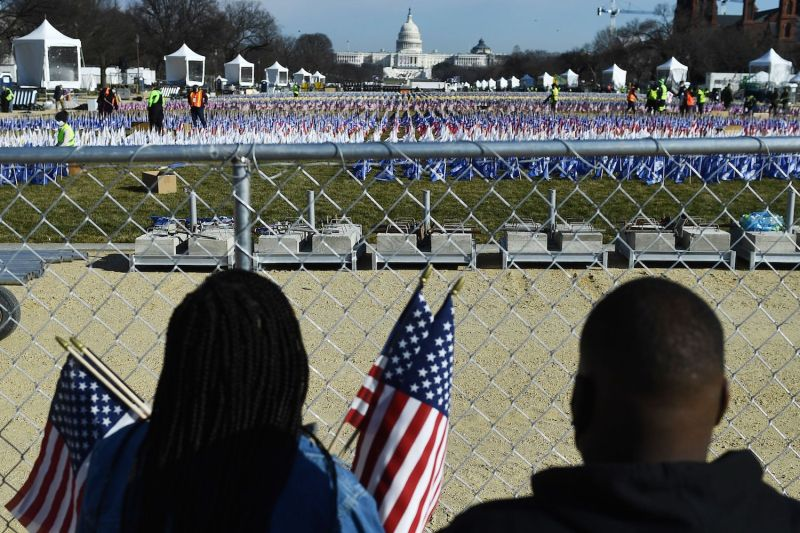 People collect flags that decorated the National Mall in Washington, DC on Jan. 21.