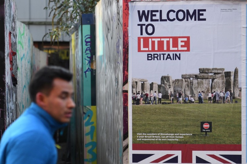 """A pedestrian walks past a """"Welcome to Little Britain"""" poster in Manchester on Jan. 5."""