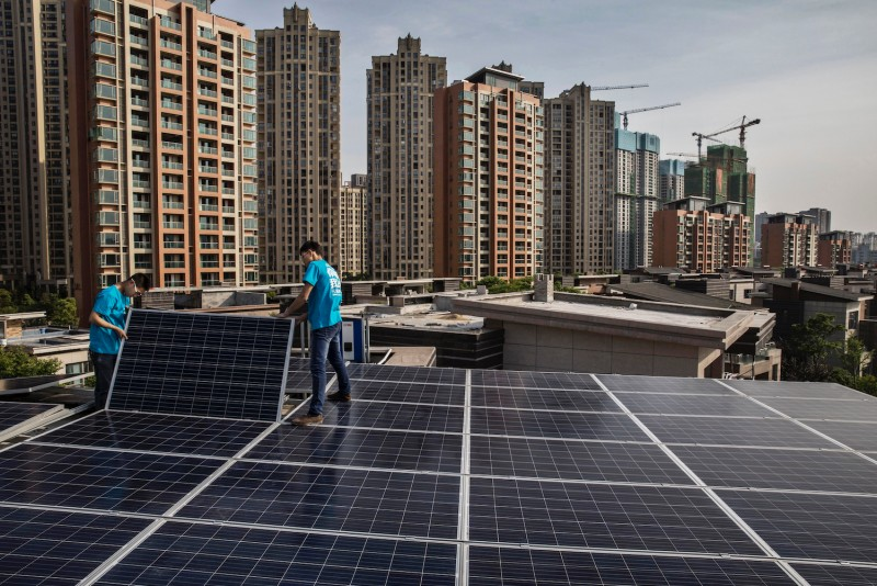 Workers from Wuhan Guangsheng Photovoltaic Company install solar panels on the roof of a building in Wuhan on April 27, 2017.