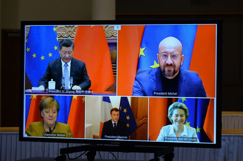 European Commission President Ursula von der Leyen, European Council President Charles Michel, German Chancellor Angela Merkel, French President Emmanuel Macron, and Chinese President Xi Jinping are seen on a screen during a video conference to approve an investment pact between China and the European Union in Brussels on Dec. 30, 2020.