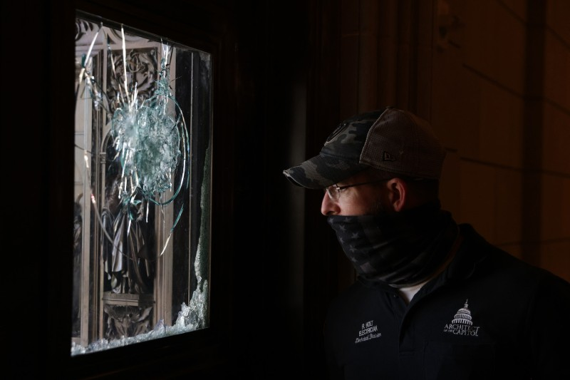 A member of the Architect of the Capitol inspects a damaged entrance of the U.S. Capitol in Washington on Jan. 7.