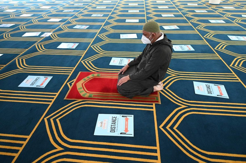A volunteer prays alone in a prayer hall with signs on the carpet enforcing social distancing at Madina Masjid in Sheffield on July 24, 2020.