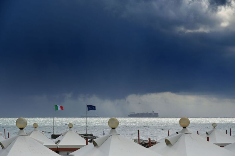 A view shows a private beach as a cargo and a container ship sail across the horizon at Venice Lido, Italy, on Sept. 7, 2020.