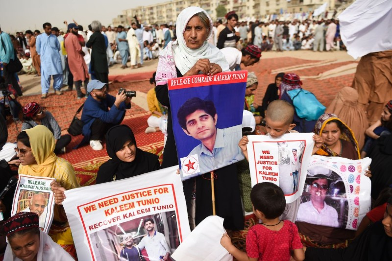 Family members of missing Pakistanis hold photos of their relatives at a Pashtun Tahafuz Movement protest rally in Karachi, Pakistan, on May 13, 2018.